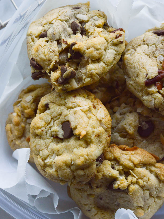Carpool Cookies are thick, hearty cookies studded with chocolate chips and pecans. They are piled into a parchment-lined food storage container, perfect for taking with you in the car!