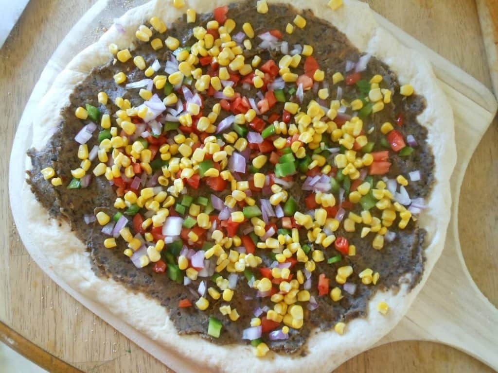 corn, peppers, and onions on pizza
