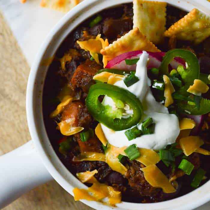 Sweet Potato Black Bean Chili with sour cream and diced jalapenos, cheese and little saltine crackers
