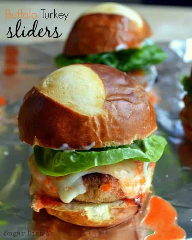 Delicious little turkey burgers loaded with buffalo flavor, topped with creamy cheese, a little lettuce for crunch, and spread with blue cheese or ranch. These Buffalo Turkey Sliders are perfect for tailgating or game day parties!