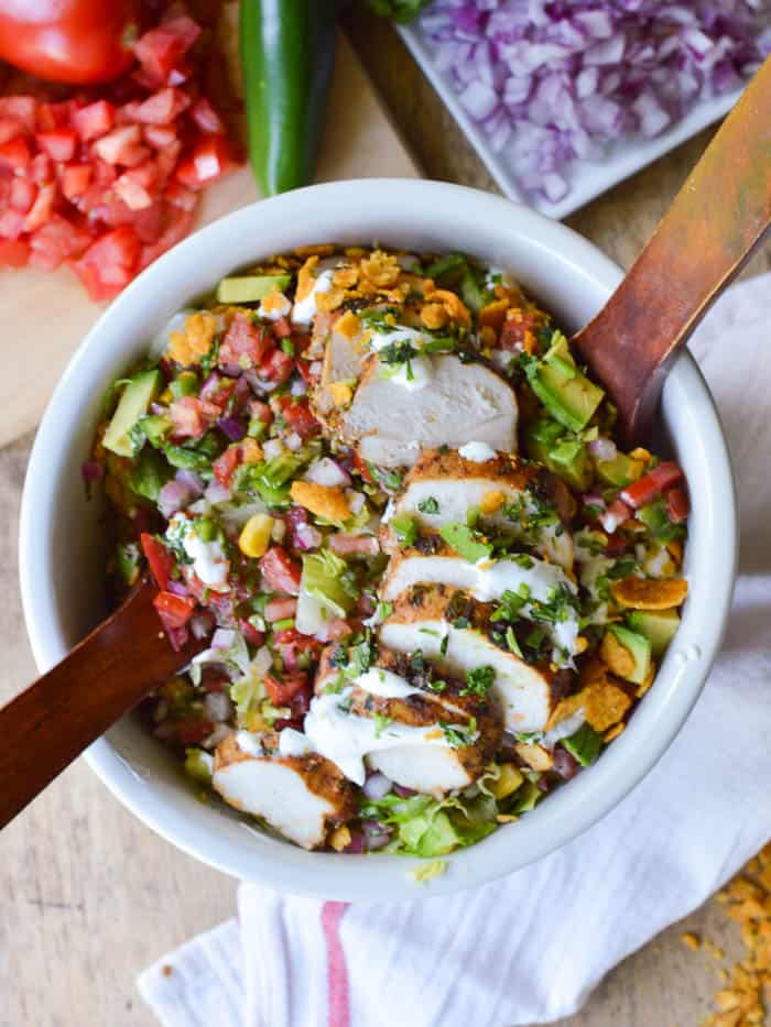 overhead view of a big bowl of southwestern chicken salad with wooden salad tongs