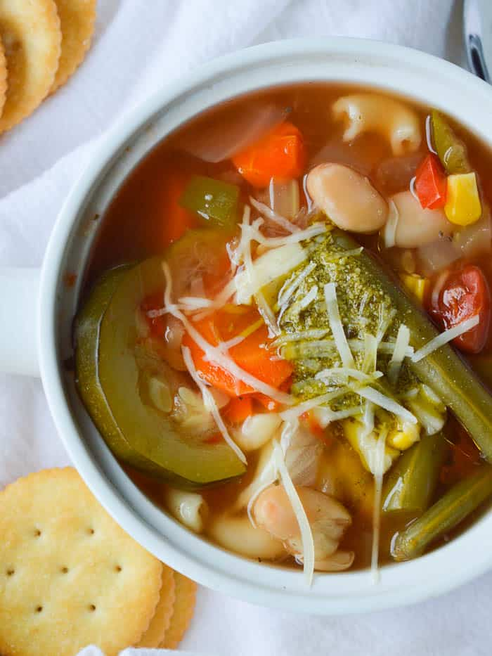 Summer Vegetable Soup with a dollop of pesto on top is colorful and loaded with garden veggies