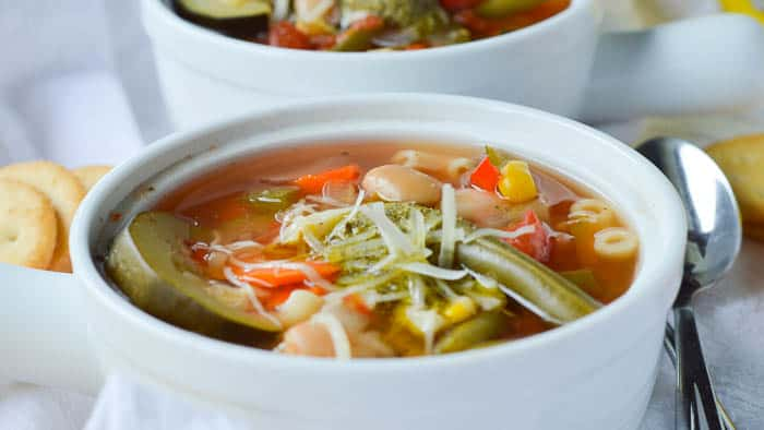 A close up look at this delicious summer vegetable soup loaded up with sliced zucchini, corn, green beans, cannellini beans, tomatoes, and more!