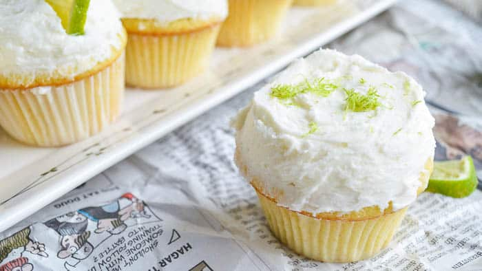 Tequila Cupcakes topped with Margarita Buttercream on a table covered in newsprint
