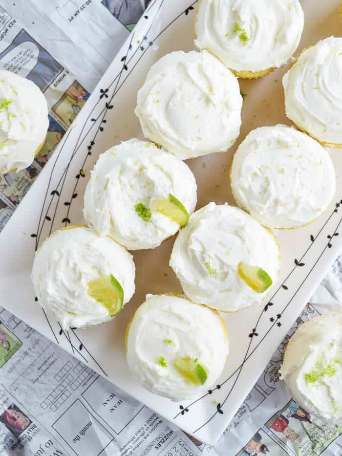 A plate of tequila cupcakes covered in whipped margarita buttercream and wedges of lime