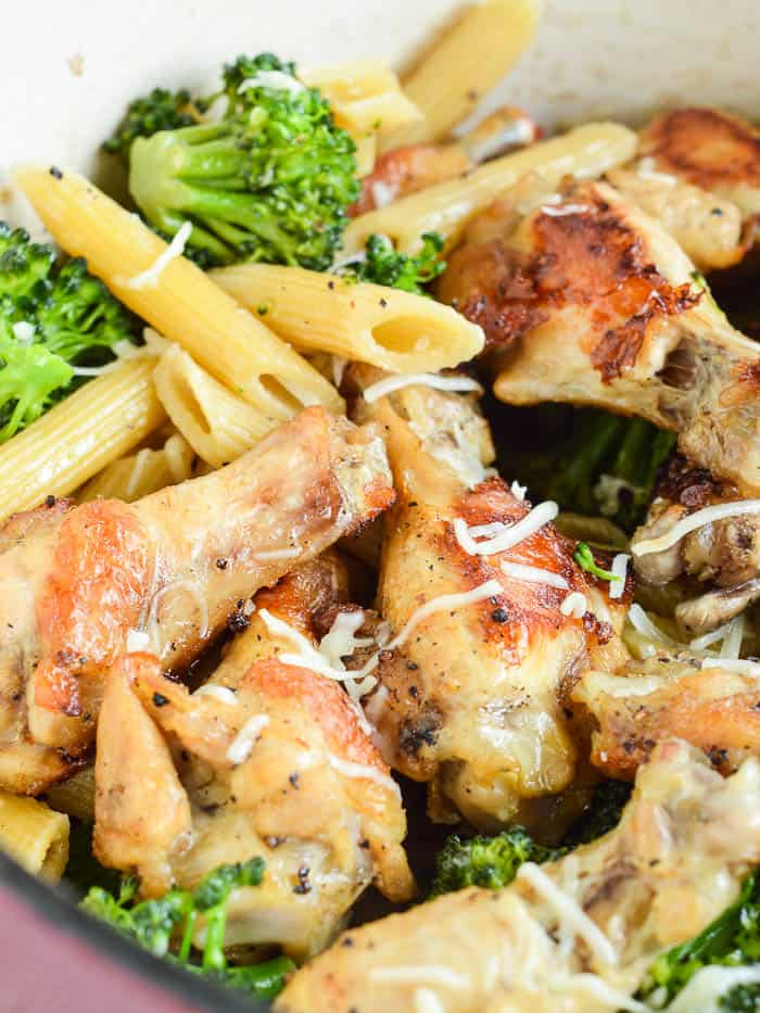 One Pot Garlic Chicken with penne and fresh broccoli in the pot, tossed with cheese, and ready to serve
