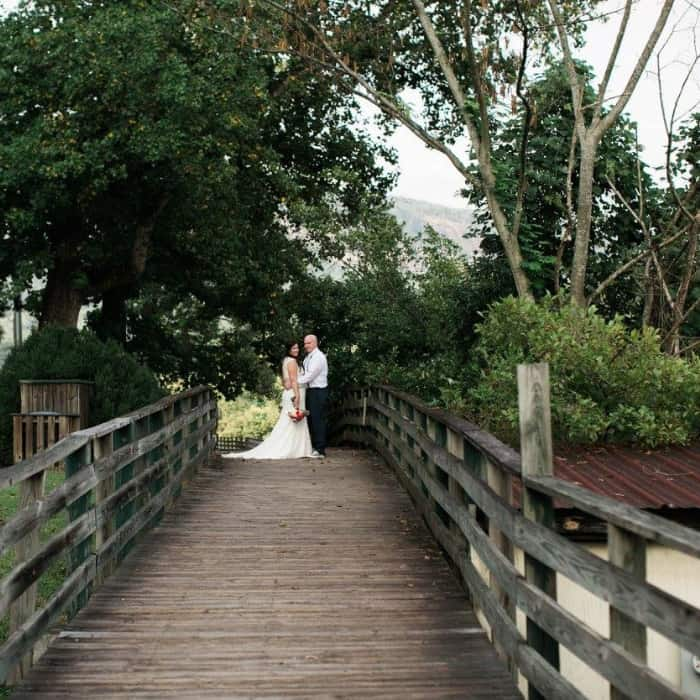 The boardwalk on Lake Lure with a bride and groom sanding beneath a halo of trees