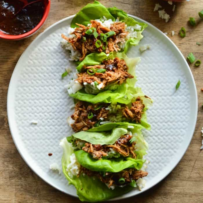 Chinese Pork lettuce Wraps overhead image; bright green Boston Bibb lettuce, tender Chinese BBQ pork, and a little sticky jasmine rice.