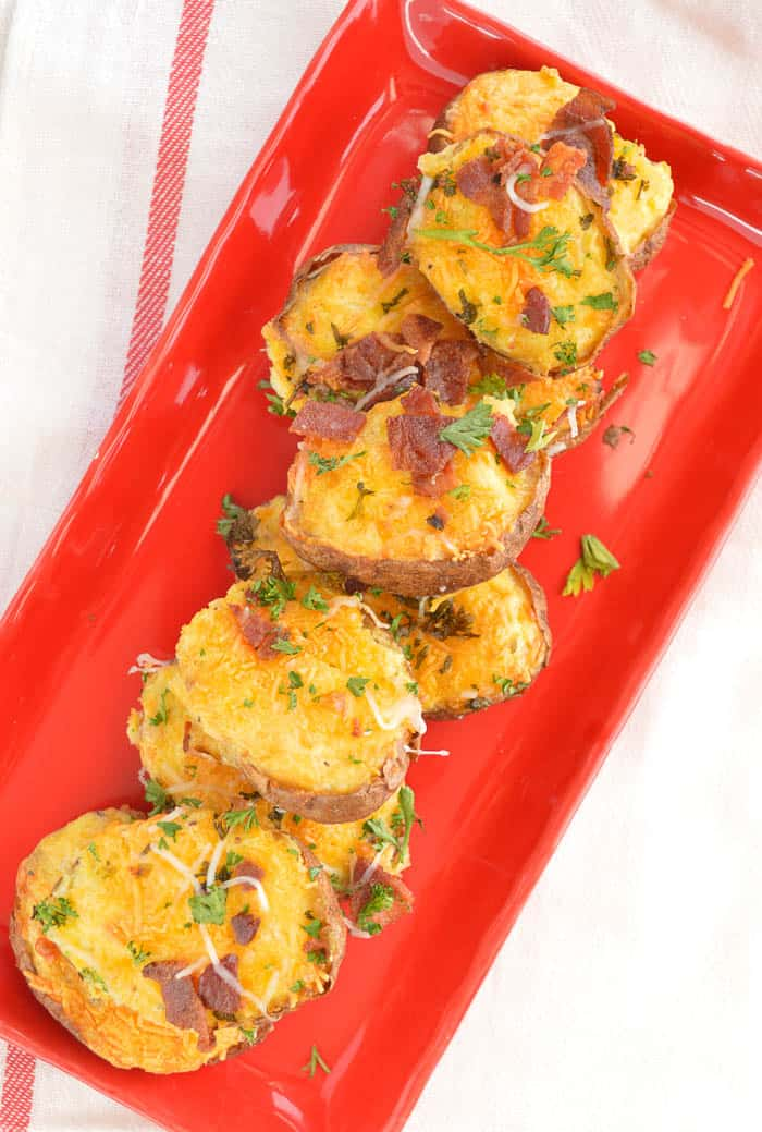 Twice Baked Breakfast Potatoes on a red plate viewed from overhead and ready to serve