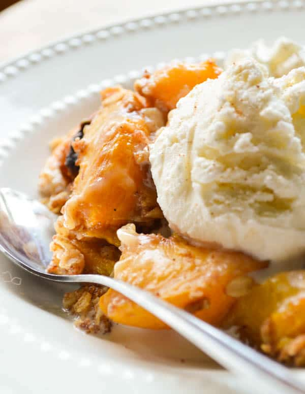 Fresh peaches are slow cooked with rum, spices, and a crumbly oatmeal topping to make this boozy peach cobbler.