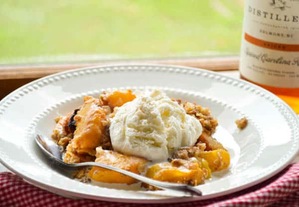 Slow cooker boozy peach cobbler with ice cream is such a delicious way to celebrate summer!