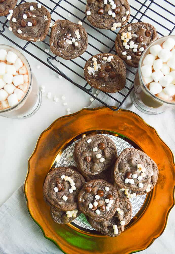 Chocolate chocolate chip cookies studded with tiny mallow bits on a gold-rimmed plate with two big cups of hot chocolate loaded with marshmallows and more cookies on a cooling rack.
