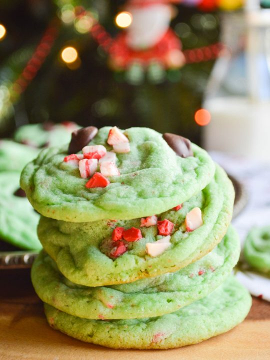 Four green cookies studded with chocolate chips and peppermint chips stacked on a table in front of a Christmas tree