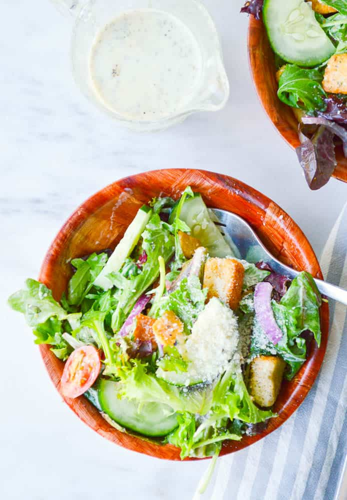 An overhead view of Italian salads in wooden bowls. The veggies are coated in my favorite Italian salad dressing