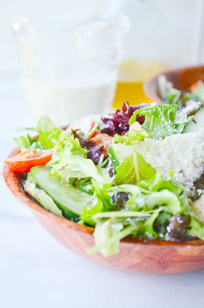 A bowl loaded with bright green lettuce, croutons, and other Italian salad veggies, coated in the best creamy Italian dressing