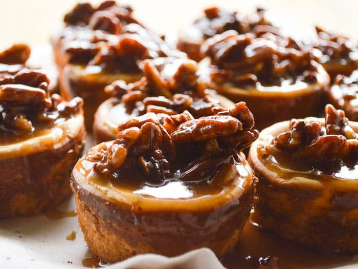 Little simple cheesecakes doused in homemade spiced rum caramel studded with pecans. Spiced Rum Pecan Cheesecakes are 4-5 bites each and decadent!