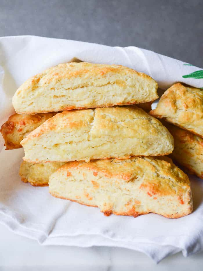Garlic Herb and Cheddar Scones stacked with a cheesecloth