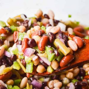 The Best Easy Bean Salad Recipe image of brightly colored bean salad on a wooden spoon