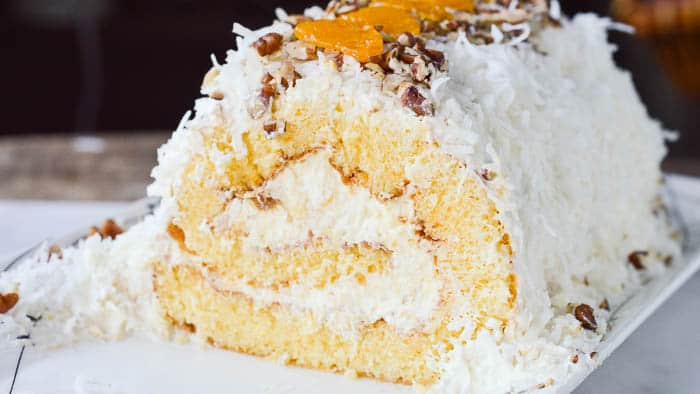Yellow sponge cake rolled and filled with pineapple fluff, mandarin oranges, and topped with coconut and pecans.