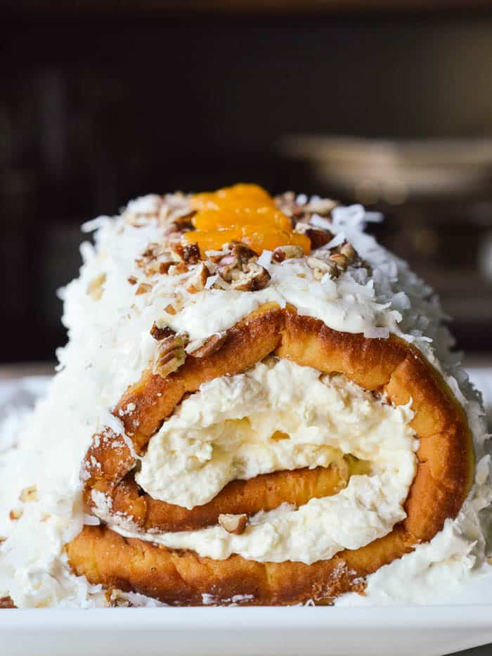 Pig Pickin Cake Roll is a twist on a mandarin orange cake with pineapple fluff frosting. It's filled, frosted, covered in coconut. and sprinkled with chopped pecans