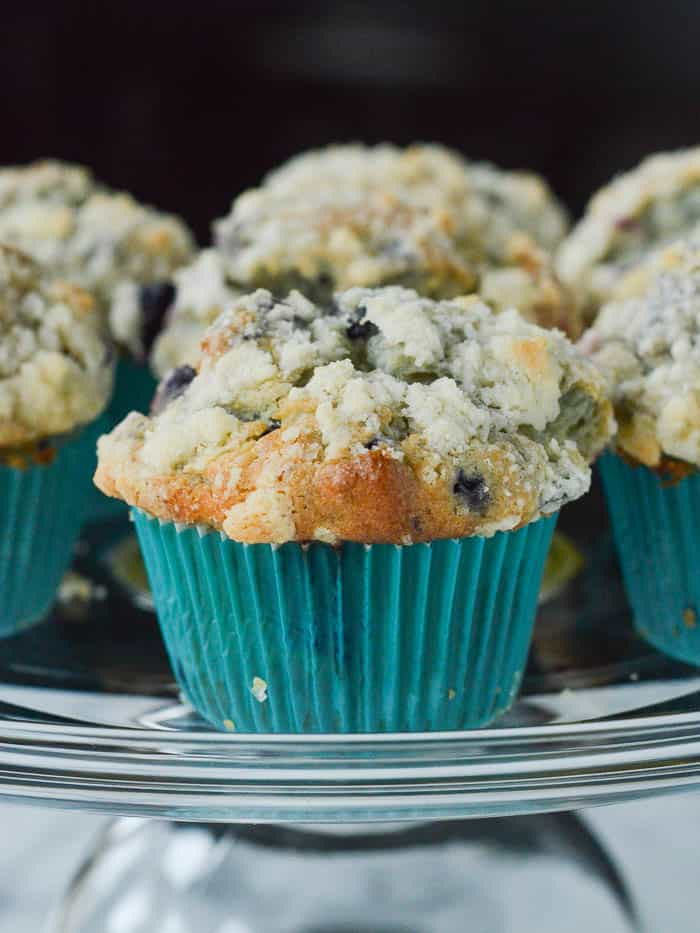 High-domed Blueberry Muffins with a gorgeous crumb topping in teal paper wrappers