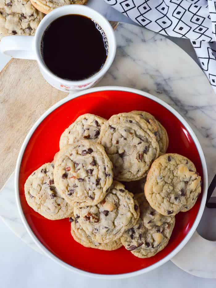 overhead view of Chocolate Chip Blondie Cookies on a red plate with a ciup of coffee to the side