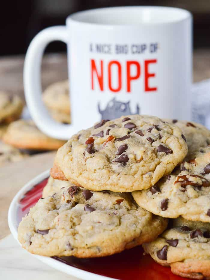 A pile of Chocolate Chip Blondie Cookies on a red plate with a funny coffee cup in the background