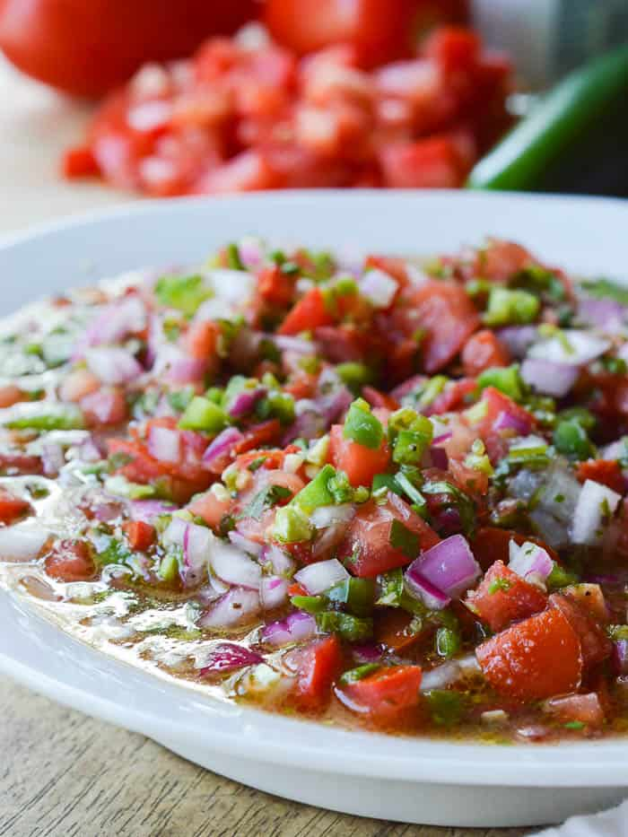 Easy Pico de Gallo ready to serve! Loads of fresh chopped Roma tomatoes, red onion, jalapeno, garlic, and cilantro