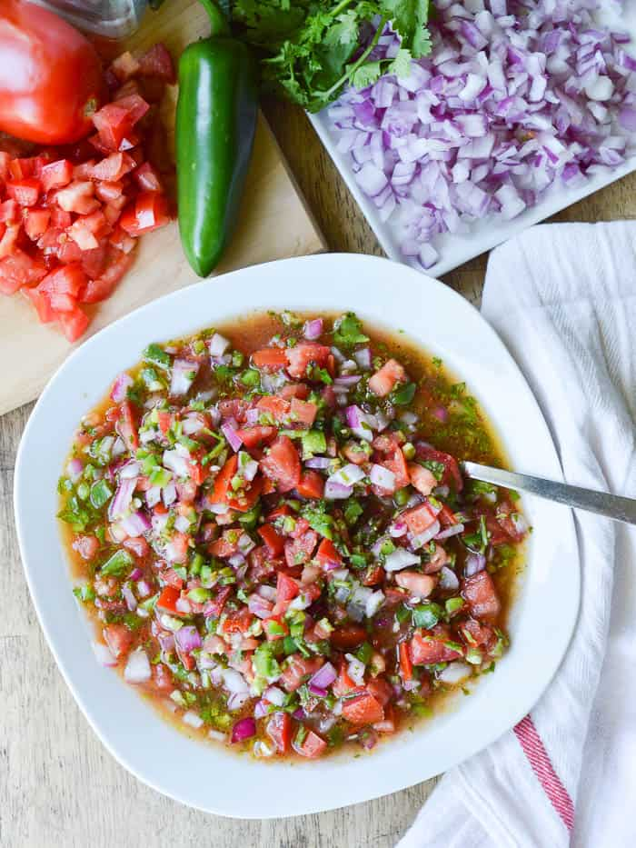 Overhead view of pico de gallo and all the ingredients needed to make it