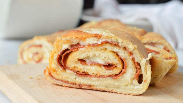 A slice of easy stromboli recipe layered with meats and cheeses wrapped and rolled in a soft dough that's baked to golden perfection
