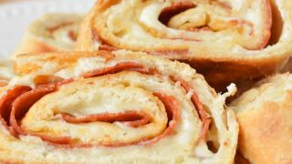 Slices of Easy Stromboli in a white dish with a red and white flour sack towel ready for serving