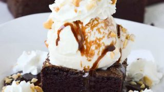 Square cropped image of the best homemade brownie sundae topped with hot fudge, whipped cream, and chopped peanuts