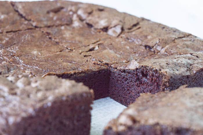A close up image of THE BEST homemade brownies. They are dense, fudgey, and super thick, perfect for sundaes.