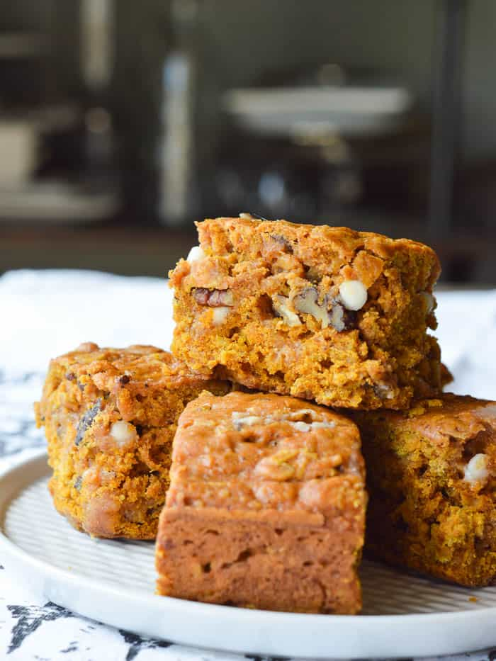 A stack of Pumpkin Cake Bars studded with white chocolate chips and chopped pecans. These bars are simple to make, super moist, and can be eaten like a bar cookie or with a fork!