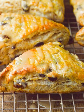 A square cropped close up image of golden brown run raisin scones, glazed and cooling on a cooling rack.