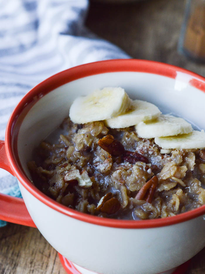 This image of banana cinnamon oatmeal shows cooked old fashioned oats mixed with chopped pecans, ripe bananas, and almond milk in a teacup. Topped with sliced bananas and ready to eat.