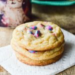 Unicorn Cake Mix Cookies stacked on a napkin next to a cup of coffee ready to eat