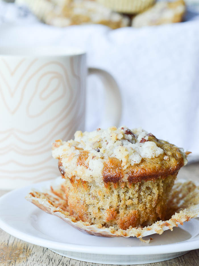 A perfectly golden and fluffy banana muffin with a crumbly pecan streusel topping sitting on a small white plate. The paper liner is peeled away so you can see the flecks of banana and there's a coffee cup in the background.