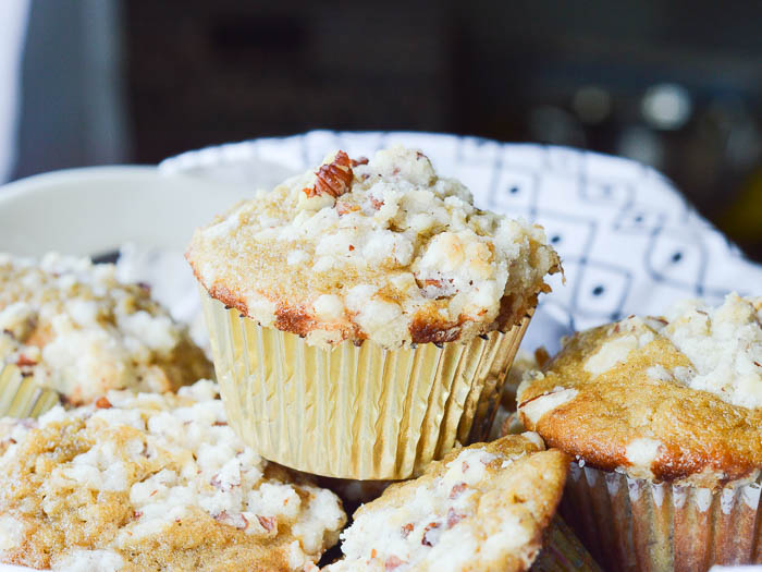 A landscape image of muffins piled in a bowl lined with a black and white tea towel. The focal point of the photo is a perfectly domed muffin in a gold paper liner with a crumbly streusel topping.