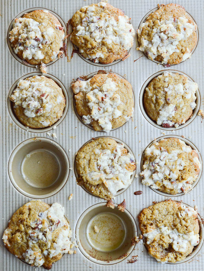 An overhead view of banana muffins  in the muffin tin, fresh from the oven. The pan holds 12 and there are two muffins missing, like as if someone needed to eat them warm right away. These banana muffins are topped with streusel and you can see bits of pecans and shredded coconut peeking through the crumbly topping.