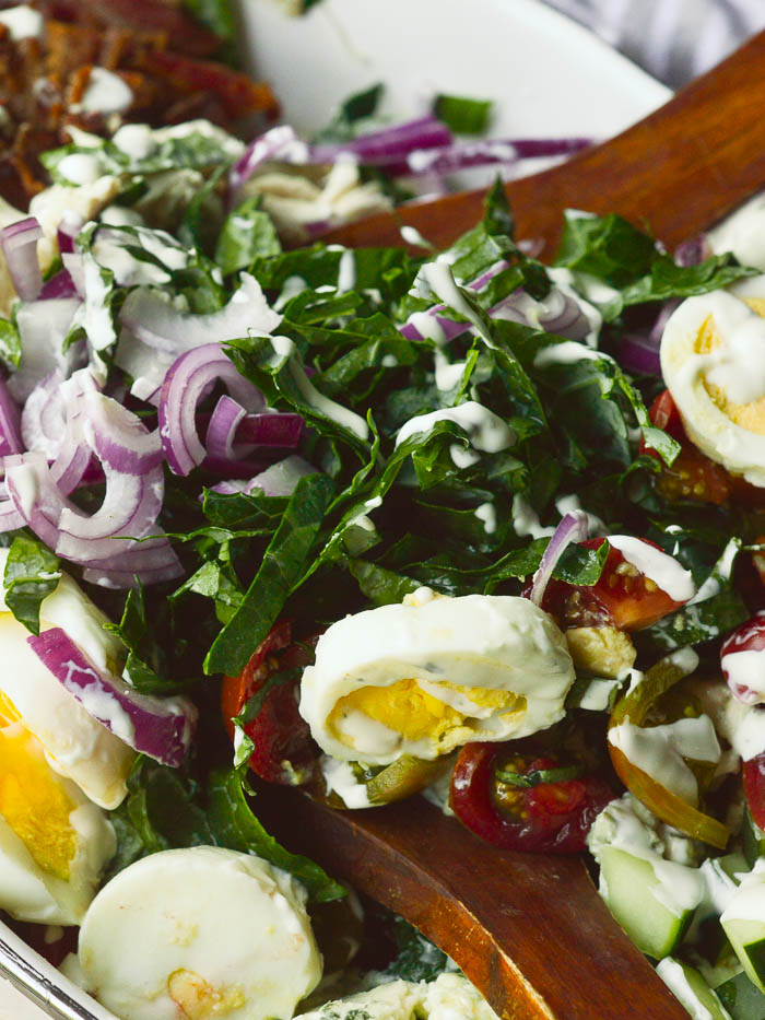 A close up of thinly chopped kale salad drizzled with ranch dressing. There are sliced hard boiled eggs, thinly sliced red onions, chopped cherry tomatoes, bacon, and cucumbers in view.