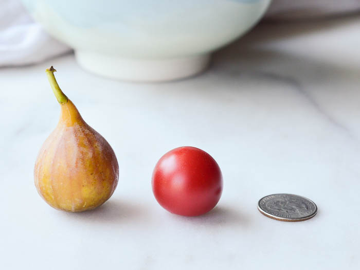 A fresh fig, a cherry tomato, and a quarter all lined up in a row so that you can see the size of the fig to scale.
