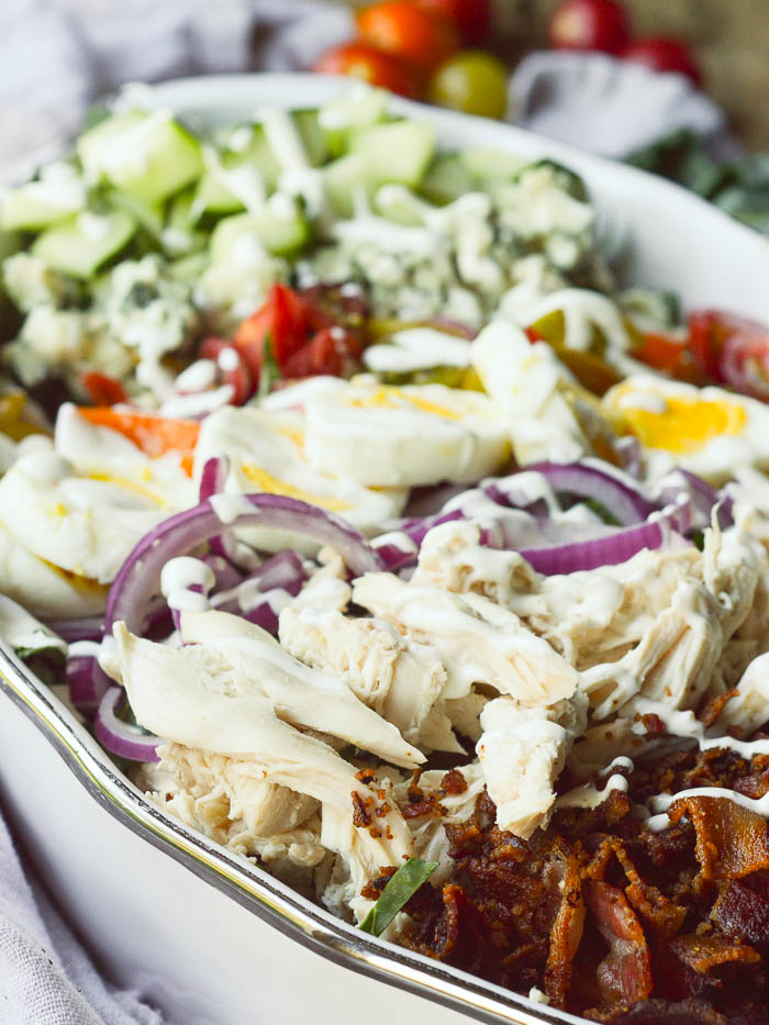 A zoomed in view of shredded rotisserie chicken, sliced red onions, sliced hard boiled eggs, chopped cherry tomatoes and cucumbers, and crumbly Roquefort cheese. Everything is drizzled with ranch dressing.