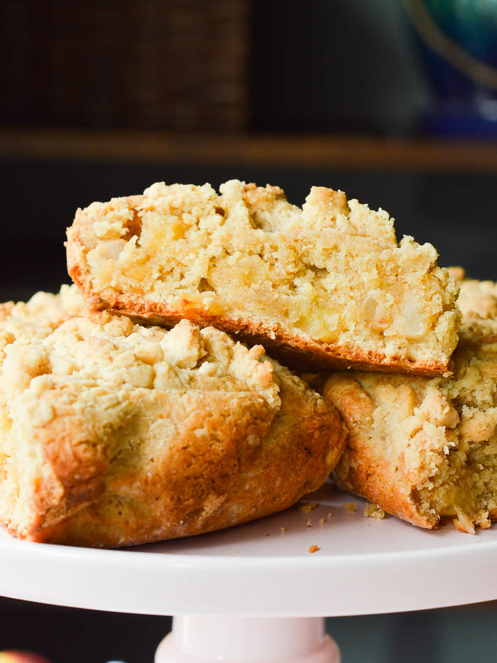 A pile of BIG FAT scones loaded with fresh apples and topped with a buttery streusel. These Apple Pie Scones are sitting atop a cake stand, and you can see the tender cumb of the scones, the crisp baked edges, and a hint of apple pie spice.