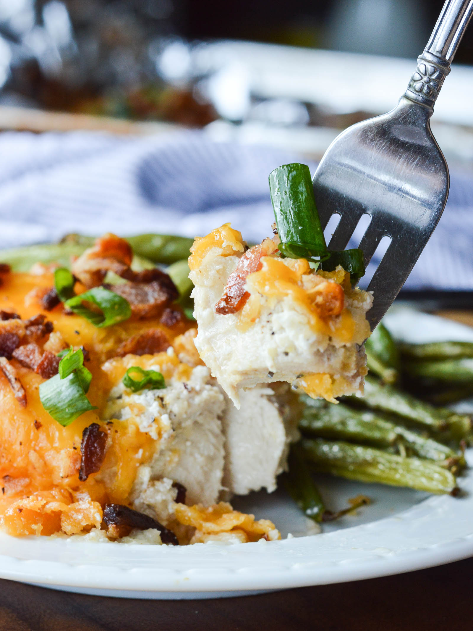 A bite of Smothered Cheesy Sour Cream Chicken on the end of a fork that hovers over the plate. You can see the layers of the chicken dish - seasoned sour cream, melted cheese, crumbled bacon, and chopped green onions.
