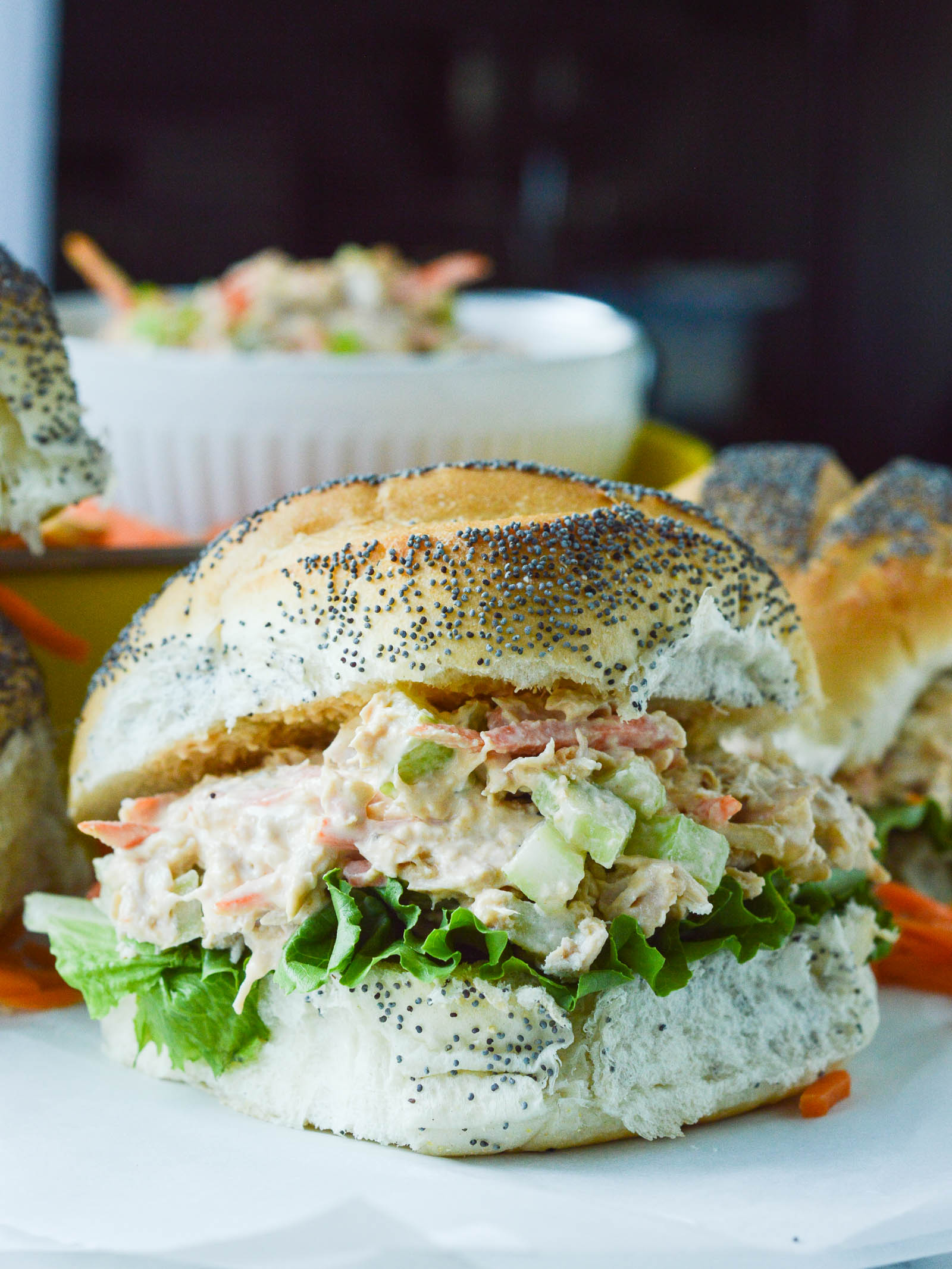 Buffalo Chicken Salad piled onto a fluffy poppy seed bun with green leafy lettuce
