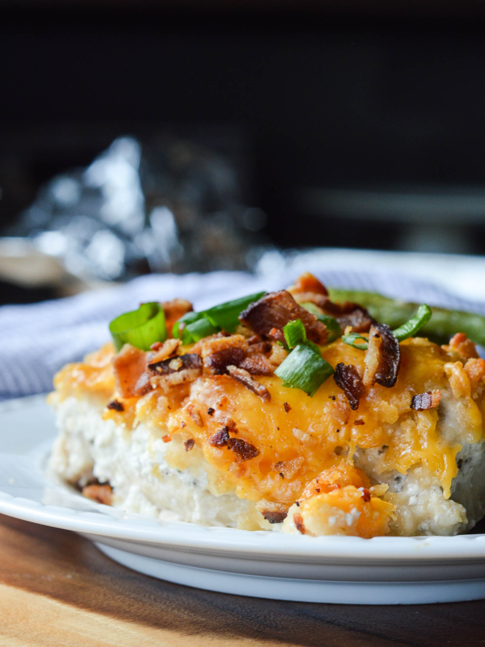 A dinner plate piled with baked chicken breast smothered in seasoned sour cream, melty cheddar cheese, chopped bacon, and chopped green onions