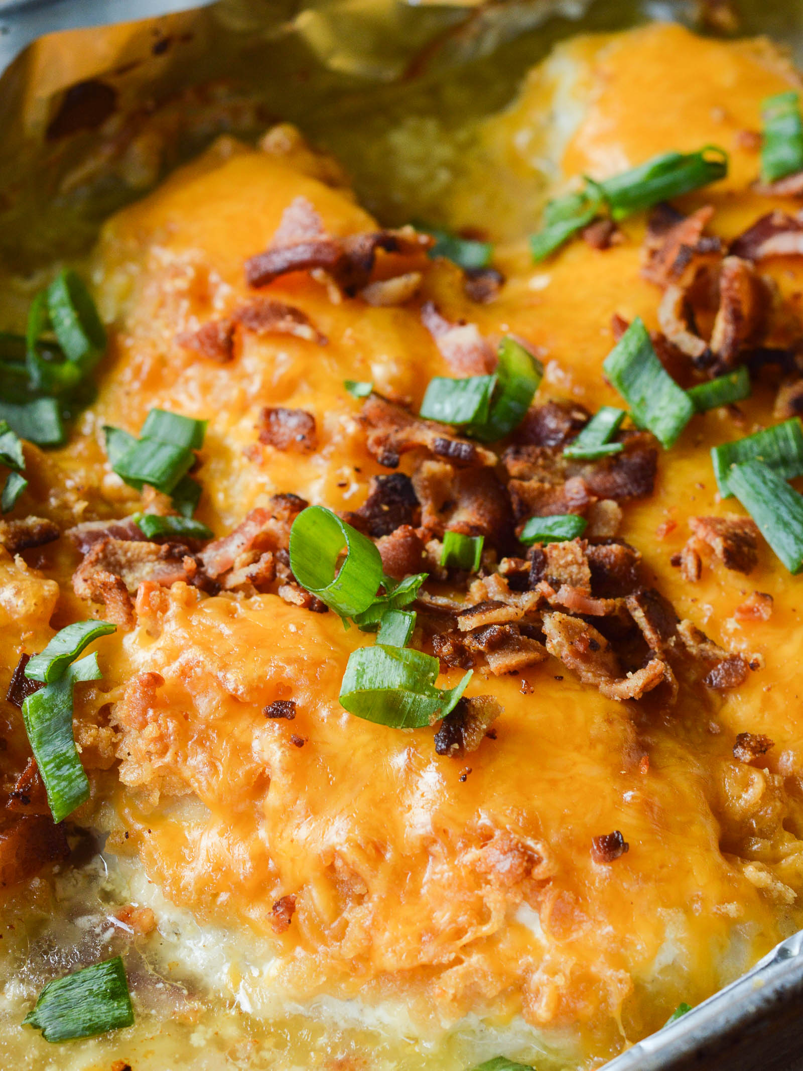 Baked chicken breasts in a foil-lined pan smothered in cheese, bacon, and green onions.