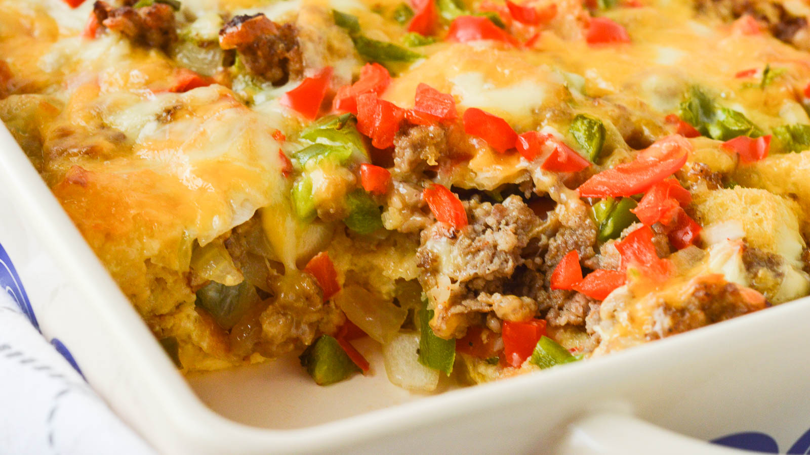 A close up image of a sausage strata, sliced, so that you can see the crumbled, cooked sausage, onions, peppers, and cheese spilling out into the empty space of the casserole dish