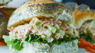 Buffalo Chicken Salad piled onto a fluffy poppy seed roll with leafy lettuce.